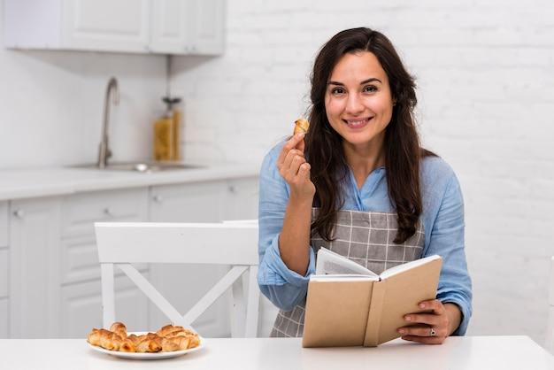 Молодая женщина читает книгу на кухне Бесплатные Фотографии