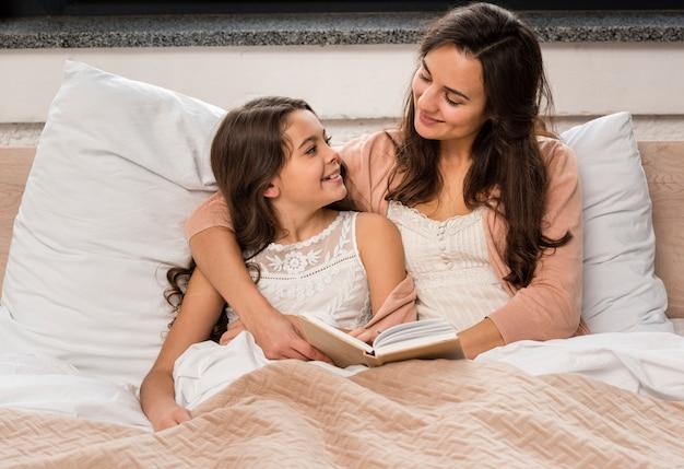 Мать и дочь читают книгу в постели Бесплатные Фотографии