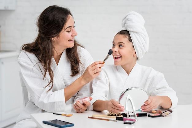 母と娘が一緒に化粧をしています 無料写真
