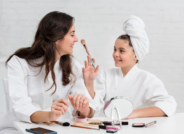 母と娘が化粧をしています 無料写真