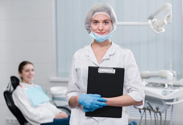 クリップボードを保持している歯科医の肖像画 無料写真