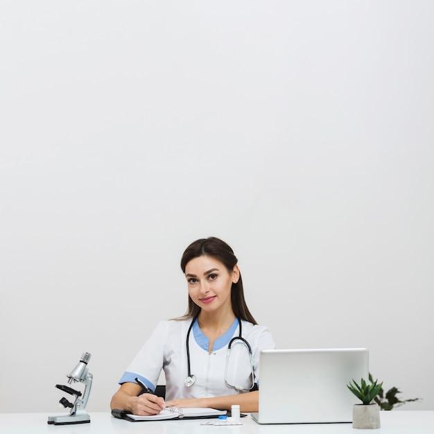 オフィスに座っている若い女性医師 無料写真