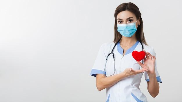 Женский доктор держит плюшевое сердце с копией пространства Бесплатные Фотографии