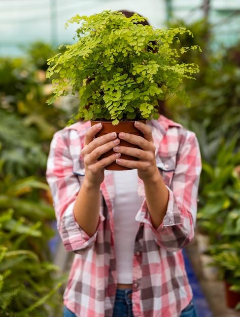 Женщина держит голову горшок в теплице Бесплатные Фотографии