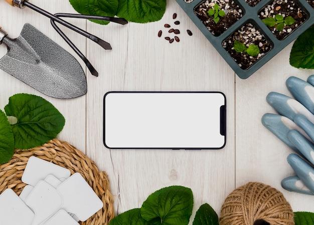Плоские садовые инструменты и растения с пустым телефоном Бесплатные Фотографии