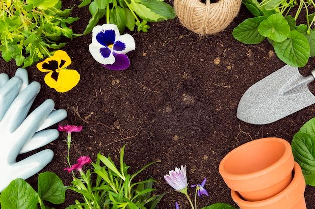 トップビューガーデニングツールとコピースペースが付いている土の植物 無料写真