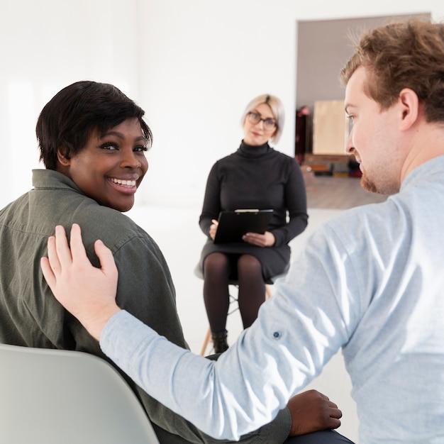 アフリカ系アメリカ人の女性患者をコンソールにしようとしている男 無料写真