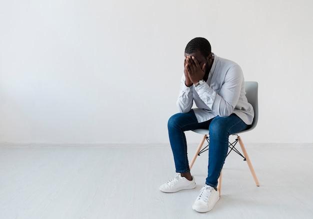 椅子に座って土アフロアメリカ人 無料写真