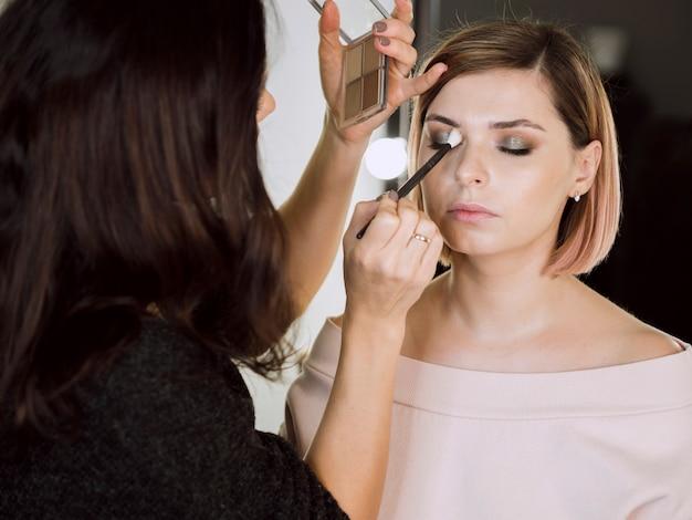 Женщина, применяя косметику на модели Бесплатные Фотографии