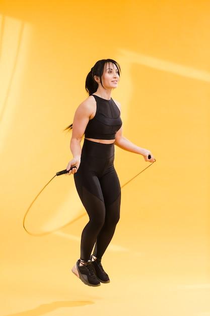 Вид сбоку спортивная женщина в тренажерном зале, прыжки через скакалку Бесплатные Фотографии