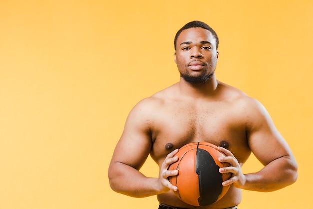 バストボールを保持している上半身裸の運動男 無料写真