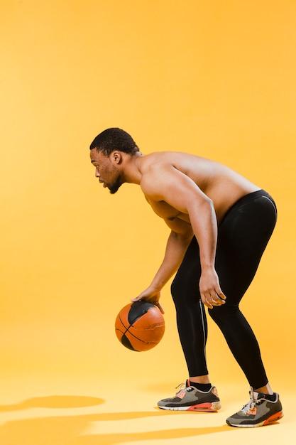 バスケットボールをしている上半身裸の運動男 無料写真
