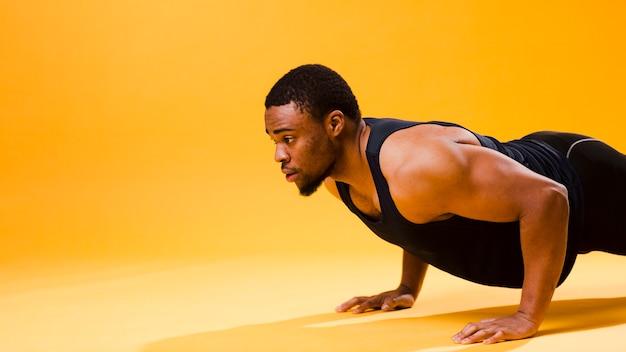 コピースペースでプッシュアップを行う運動の男の側面図 無料写真