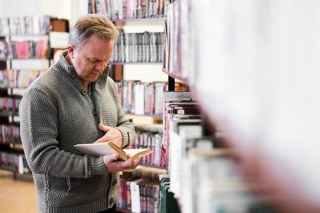 Сосредоточенный старший мужчина, глядя на книгу Бесплатные Фотографии