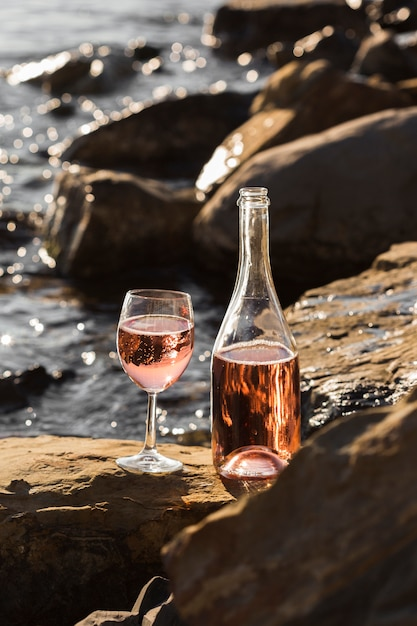 Вид спереди рюмки и бутылки на скалах океана Бесплатные Фотографии