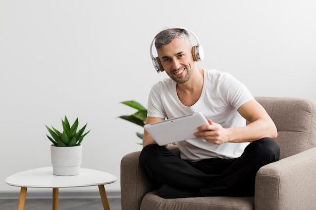 椅子に座ってデジタルタブレットを保持している男 無料写真