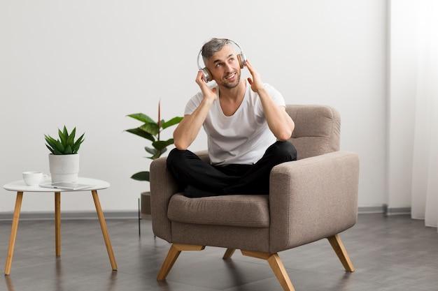 Улыбающийся парень сидит на стуле и слушает музыку Бесплатные Фотографии