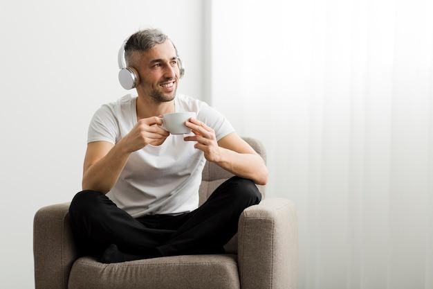 一杯のコーヒーを保持しているヘッドフォンで正面男 無料写真
