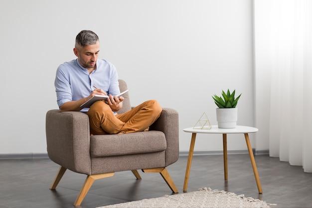 椅子に座って、彼の議題に書く男 無料写真