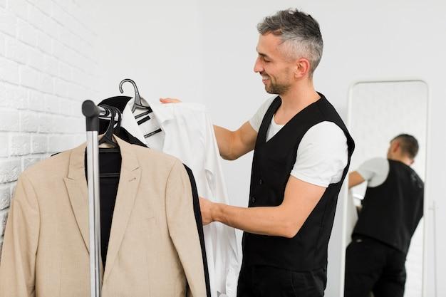 Боком мужчина расставляет одежду на вешалках Бесплатные Фотографии