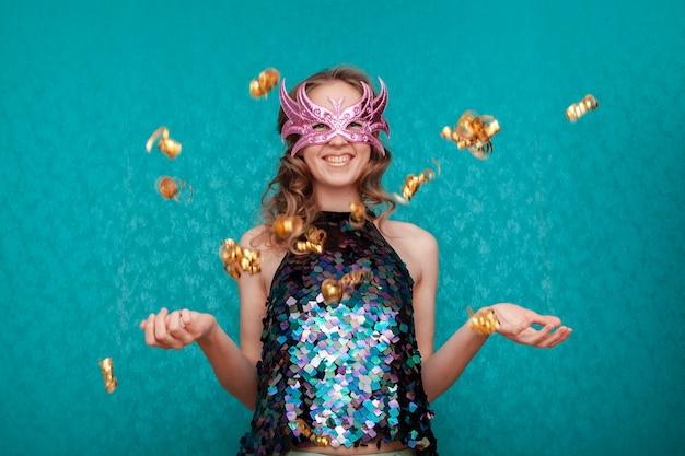 ピンクのマスクと金色の紙吹雪と幸せな女 無料写真