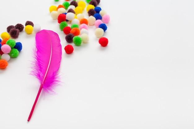 カラフルなコットンボールとピンクの羽のコピースペース 無料写真