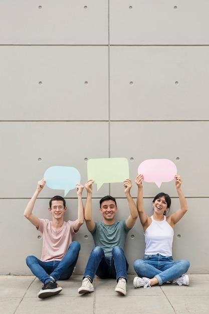 Молодые люди держат красочные речи пузыри Бесплатные Фотографии