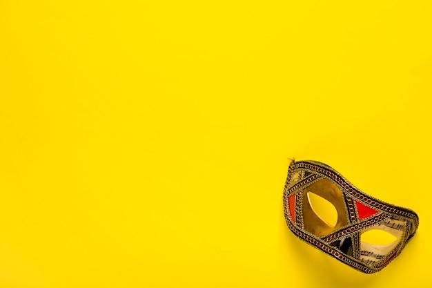 コピースペースと黄色の背景に黄金のマスク 無料写真