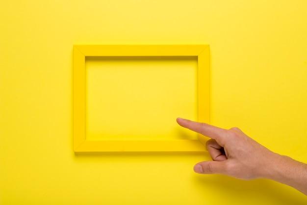 黄色の空のフレームを指している人 無料写真