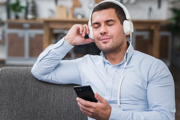 音楽を聞いている男性の正面図 無料写真