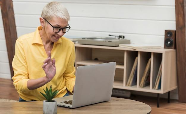 彼女のラップトップでインターネットを探している美しい年配の女性 無料写真