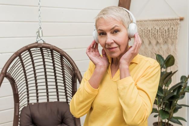 Старшая женщина слушая к музыке хотя белые наушники Бесплатные Фотографии