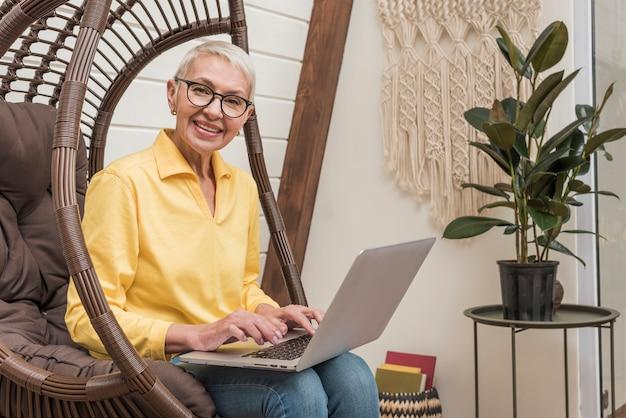 スマイリーの年配の女性が彼女のラップトップに取り組んで 無料写真