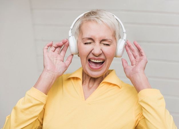 Старшая женщина слушает громкую музыку Бесплатные Фотографии