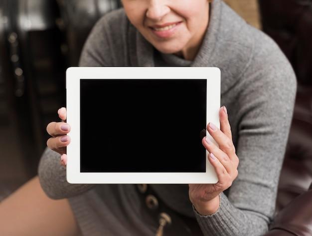 空のタブレットを保持しているスマイリー年配の女性 無料写真