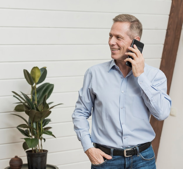 Вид спереди зрелый человек разговаривает по телефону Бесплатные Фотографии