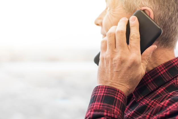 電話のクローズアップで話しているサイドビュー中年の男性 無料写真