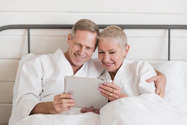 ベッドでタブレットを探している成熟したカップル 無料写真