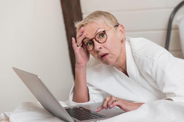 ベッドでノートパソコンを使用して成熟した女性 無料写真