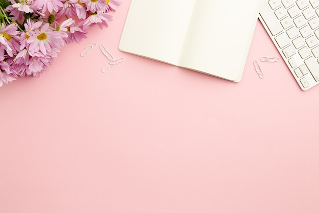 空のノートブックで働く女性ピンクデスク 無料写真