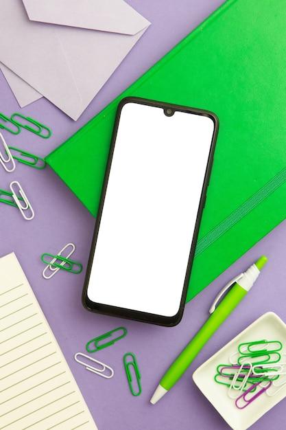 空の電話で紫色の背景にフラットレイアウト職場配置 無料写真