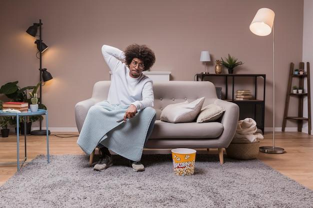 テレビを見てソファの上の若い男 無料写真