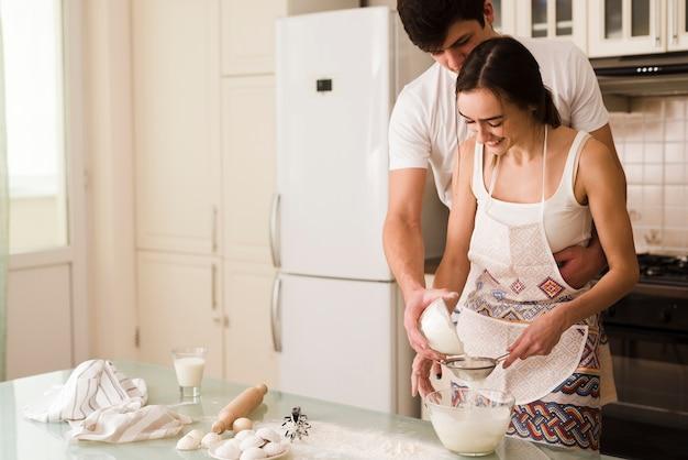 Прелестный молодой мужчина и женщина вместе готовить Бесплатные Фотографии