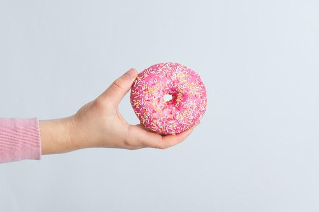 振りかけると艶をかけられたドーナツを持っている手の正面図 無料写真