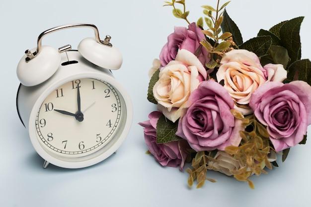 時計の横にあるバラの花束 無料写真