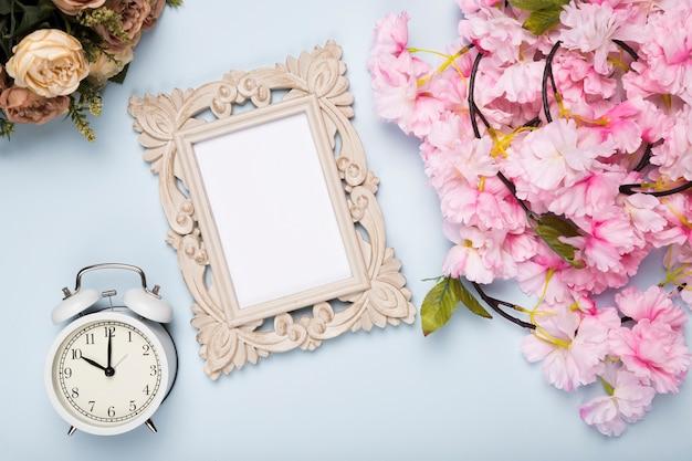 時計とフレームの横にあるトップビューの花 無料写真