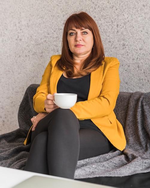 Красивая деловая женщина, наслаждаясь кофе Бесплатные Фотографии