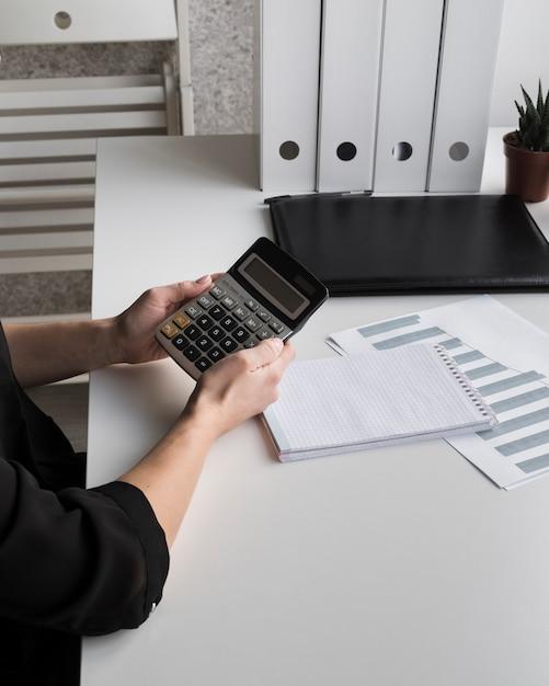 Высокий угол бизнес женщина, держащая калькулятор Бесплатные Фотографии