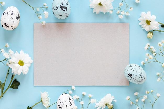 Рамка из цветов с листом бумаги и яйцами Бесплатные Фотографии