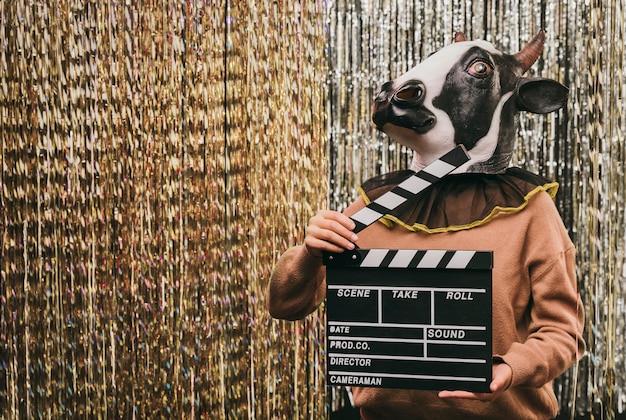 映画のスレートと牛の衣装の女性 無料写真